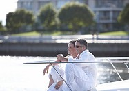 Mature couple sitting on yacht´s bow, drinking wine