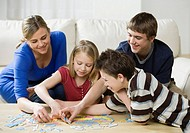 Mother and children doing puzzle