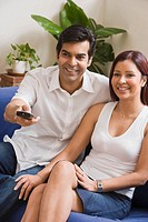Smiling couple watching television