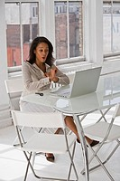 Businesswoman using laptop at home