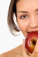 Close-up of a young woman biting into an apple