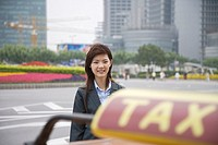 China, Shanghai, young businesswoman in front of taxi, portrait