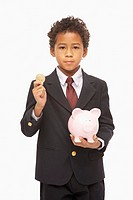 Boy 8-9 dressed as businessman holding piggy bank, portrait