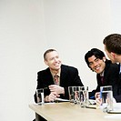 People laughing at business meeting