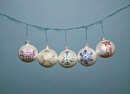 Five Christmas ornaments hanging on string, close-up