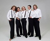 Five mature women wearing trousers and white shirts, smiling