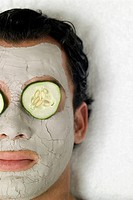 Person with a face mud mask and cucumber slices on the eyes