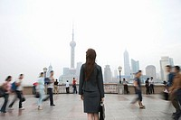 China, Shanghai, businesswoman looking at city skyline, people walking blurred motion