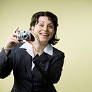 Mature woman in suit preparing to take photograph