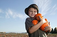 Portrait of boy 6-7 holding small pumpkins in fields, smiling