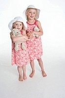 Portrait of two blond girls with hats and their toy animal (thumbnail)