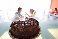 Chocolate cake on bench in cafe, couple in background