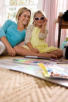 Mother smiling at daughter 6-8 wearing sunglasses indoors, ground view