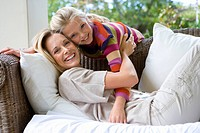 Girl 6-8 leaning over sofa hugging mother, smiling, portrait