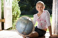 Girl 8-10 sitting with globe by French doors, smiling, portrait