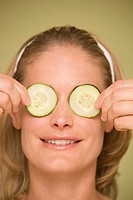 Young woman holding cucumber slices over eyes, close-up