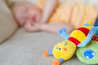 Baby girl 12-15 months asleep on sofa, toys in foreground differential focus