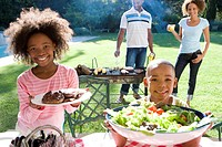 Family of four having barbeque, portrait of brother and sister 6-10 smiling