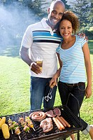 Man embracing woman by barbeque, smiling, portrait (thumbnail)