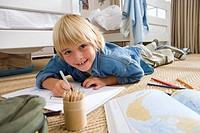 Boy 6-8 in bedroom drawing, smiling, portrait