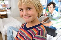 Father and son 6-8 in bedroom, smiling, portrait, close-up of boy