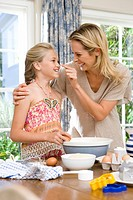 Mother and daughter 8-10 baking, mother touching daughter´s nose, smiling