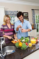Young man and woman making salad by jug of juice, smiling