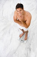 Man in underwear on bathroom scales, smiling, portrait, elevated view