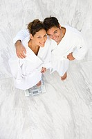 Young couple in bathrobes, man embracing woman on bathroom scales, smiling, portrait, elevated view
