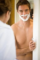Man preparing to shave, smiling at woman differential focus