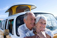 Senior couple embracing by camper van, smiling