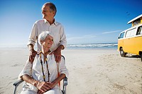 Senior couple on beach by camper van, man behind woman in chair, smiling
