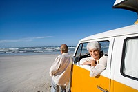 Senior couple on beach, woman in camper van, smiling, portrait