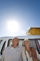 Senior couple arm in arm against camper van, low angle view