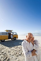 Senior couple on beach by camper van, smiling, portrait (thumbnail)
