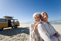 Senior woman embracing senior man from behind on beach by camper van, smiling, portrait