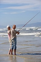 Senior couple fishing at beach, smiling, portrait