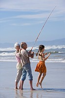 Girl 7-9 by grandparents fishing on beach, portrait of senior woman (thumbnail)