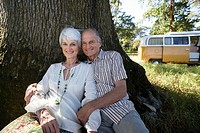 Senior couple reclining against tree in field, camper van in background, smiling, portrait
