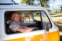 Senior couple in camper van, smiling, portrait