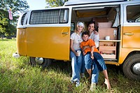Family of three in camper van, boy 10-12 on father's lap, smiling, portrait