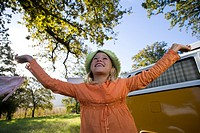 Girl 9-11 with arms raised by camper van in field, smiling, low angle view