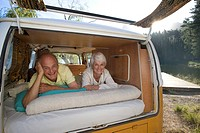Senior couple lying in back of camper van, smiling, portrait