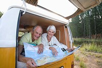 Senior couple lying in back of camper van reading map, smiling, portrait, low angle view