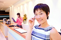 Woman in headset by reception desk, colleague in background, smiling, portrait
