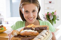 Young woman with plate of pastries, smiling, portrait, close-up