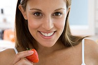 Young woman with strawberry, smiling, portrait