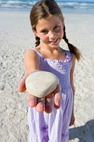 Girl 5-7 with shell on beach, smiling, portrait differential focus (thumbnail)