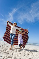 Mother and daughter 5-7 holding up blanket on beach, smiling, low angle view