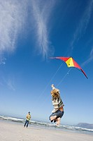 Boy 6-8 jumping by father flying kite on beach, rear view